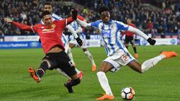 Bek Manchester United, Chris Smalling (kiri) menutup ruang tembak pemain Huddersfield, Terence Kongolo pada putaran kelima Piala FA di John Smith stadium, Huddersfield, (17/2/2018). Manchester United menang 2-0. (AFP/Oli Scarff)