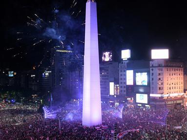 Suporter River Plate merayakan gelar juara Copa Libertadores di Obelisk, Buenos Aires, Argentina, Minggu (9/12). River Plate merebut gelar juara Copa Libertadores usai menaklukkan Boca Juniors dengan skor 3-1. (AP Photo/Gustavo Garello)
