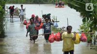 Warga berjalan melintasi banjir di Desa Sindangsari, Kabupaten Bekasi, Jawa Barat, Rabu (24/2/2021). Tim Tanggap Bencana Land Rover Club Indonesia (LRCI) melakukan drop logistik dan mengevakuasi warga yang sakit di Desa Sindangsari. (merdeka.com/Imam Buhori)