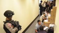 Petugas Kepolisian berjaga saat anggota Bareskrim melakukan penggeledahan di Kantor SKK Migas, Jakarta, Selasa (5/5/2015). Penggeledahan ini terkait tindak pidana korupsi dan pencucian uang yang dilakukan SKK Migas. (Liputan6.com/Herman Zakharia)