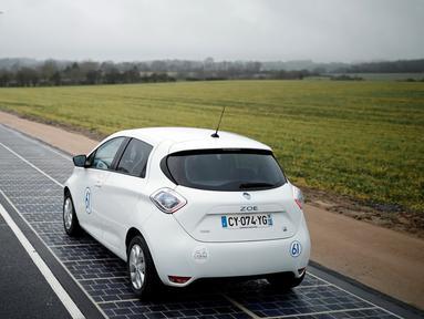 Kendaraan melintasi jalan raya berpanel surya di Tourouvre, Normandia (22/12). Jalan sepanjang 1 kilometer arah Tourouvre-au-Perche ditutupi 2.800 meter persegi panel surya yang mampung menghasilkan listrik. (Reuters/Benoit Tessier)