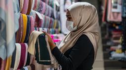 Pekerja mengenakan masker sebagai tindakan pencegahan penyebaran Covid-19 merapikan kerudung menjelang Idul Fitri yang menandai berakhirnya bulan suci Ramadan di Kuala Lumpur (13/5/2020). (AFP/Mohd Rasfan)