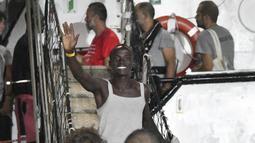 Seorang pria melambai sambil tersenyum ketika turun dari kapal penyelamat Open Arms di pulau Sisilia Lampedusa, Italia (20/8/2019). Sebelumnya permintaan untuk berlabuh di Italia ditolak, kapal Open Arms yang membawa imigran Afrika akhirnya diizinkan. (AP Photo/Salvatore Cavalli)