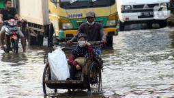 Warga menggunakan becak melintasi genangan banjir rob yang menggenangi kawasan Pelabuhan Nizam Zachman, Muara Baru,  Jakarta, Jumat (5/6/2020). Banjir rob di Pelabuhan Muara Baru tersebut terjadi akibat cuaca ekstrem serta pasang air laut. (Liputan6.com/Helmi Fithriansyah)