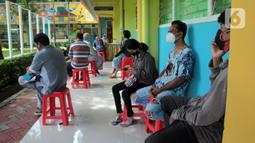 Orangtua murid menunggu untuk pendaftaran daring PPDB tahun ajaran 2021/2022 di Posko Pelayanan PPDB Jakarta Selatan, SMA Negeri 70 Bulungan, Jakarta, Senin (21/6/2021). Pendaftaran PPDB jalur zonasi untuk SD di DKI mulai dibuka pada 21-23 Juni 2021. (Liputan6.com/Herman Zakharia)