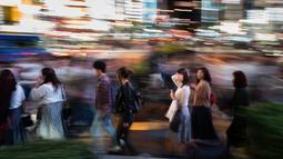 Foto pada 22 September 2018 menunjukkan orang-orang berjalan di distrik Shinjuku, Tokyo. Sebagai pusat pemerintahan Tokyo, Shinjuku memang menawarkan aktivitas malam yang seakan tidak pernah padam. (AFP PHOTO / Martin BUREAU)