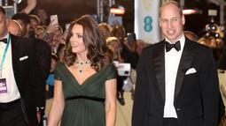 Kate Middleton didampingi Pangeran William berjalan di karpet merah acara penghargaan film British Academy Film Awards (BAFTA) 2018 di London, Minggu (18/2). Kate mengenakan dress panjang berwarna hijau lumut karangan Jenny Packham. (AP/Antonio Calanni)