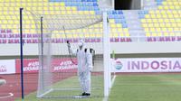 Petugas menyemprotkan disinfektan sebelum dimulainya pertandingan antara Persikabo 1973 melawan Arema FC pada ajang Piala Menpora 2021 di Stadion Manahan, Solo, Minggu (21/3/2021). (Bola.com/M Iqbal Ichsan)