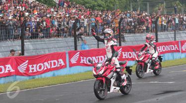 Pebalap Repsol Honda Marc Marquez dan Dani Pedrosa menyapa penggemarnya saat beraksi di Sentul, Jabar, Minggu (14/2/2016). Marquez dan Pedrosa memberikan aksi dan kejutan bagi para fans mereka yang berada di Indonesia. (Liputan6.com/Angga Yuniar)