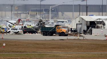 Operasi penyelamatan berlangsung di mana pesawat pengebom era Perang Dunia II milik Amerika Serikat jatuh di Bandara Internasional Bradley, Connecticut, Rabu (2/10/2019). Akibat insiden ini, setidaknya tujuh orang tewas. (AP Photo/Jessica Hill)