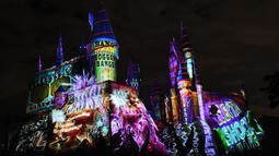 Cahaya warna-warni menghiasi kastil Dunia Harry Potter dihiasi cahaya biru di Universal Studios Hollywood, Universal City (16/11). Pertunjukan ini bertemakan 'The Magic of Christmas at Hogwarts Castle'. (AFP Photo/Chris Delmas)