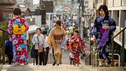 Sejumlah wanita memakai pakaian tradisional berjalan di sepanjang jalan perbelanjaan Yanaka Ginza di pusat Tokyo (30/9/2019). Wilayah Yanaka di ibukota Jepang dikenal sebagai salah satu yang paling kuno dan unik. (AFP Photo/Odd Andersen)