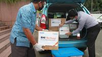 Pegawai BNI sedang memuat bantuan alat medis ke dalam mobil taksi yang akan dikirimkan ke Rumah Sakit Angkatan Laut Mintoharjo dan Rumah Sakit Polri Kramat Jati di Jakarta, Rabu 8 April 2020.