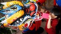Seorang anak sedang memberikan angpau kepada liong saat kirab barongsai dan long menyambut Cap Go Meh di Solo Sabtu (8/2).(Liputan6.com/Fajar Abrori)
