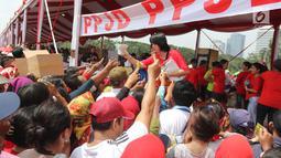 "Panitia memberikan kaos kaki gratis dalam acara ""Untukmu Indonesia"" di lapangan Monas, Jakarta, Sabtu (28/4). Acara ini dimeriahkan oleh sejumlah kegiatan seperti pertunjukkan seni dan khitanan massal. (Liputan6.com/Arya Manggala)"