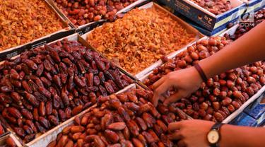 Penjual kurma merapihkan kurma dagangannya di kawasan Tanah Abang, Jakarta, Selasa (6/6). Selama bulan Ramadan, penjualan kurma di kawasan tersebut meningkat 30%, yang dihargai Rp35ribu - Rp350ribu perkilogram. (Liputan6.com/Immanuel Antonius)
