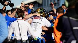 Tim Suzuki Esctar dan Joan Mir melakukan selebrasi usai balapan MotoGP Valencia di Sirkuit Ricardo Tormo, Minggu (15/11/2020). Meski finis ketujuh, Joan Mir berhasil mengunci gelar juara dunia MotoGP 2020. (AFP/Lluis Gene)
