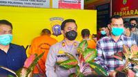 Kepala Polsek Payung Sekaki, Pekanbaru, memegang barang bukti pencurian tanaman hias. (Liputan6.com/M Syukur)