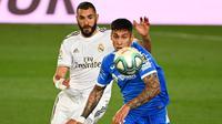 Penyerang Real Madrid, Karim Benzema, berebut bola dengan bek Getafe, Mathias Olivera, pada laga lanjutan La Liga pekan ke-33 di Stadion Alfredo Di Stefano, Jumat (3/7/2020) dini hari WIB. Real Madrid menang 1-0 atas Getafe. (AFP/Gabriel Bouys)
