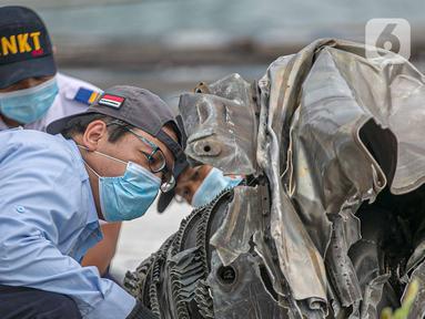 Petugas Komisi Nasional Keselamatan Transportasi (KNKT) memeriksa bagian turbin pesawat Sriwijaya Air dihari kelima yang jatuh di perairan Pulau Seribu, di Dermaga JICT, Jakarta,  Rabu (13/1/2021). Pemeriksaan itu dilakukan untuk mengetahui penyebab jatuhnya pesawat. (Liputan6.com/Faizal Fanani)