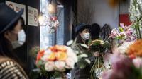 Penjual bunga Zhao Yuanyuan mengenakan masker mengatur bunga menjelang Hari Valentine di tokonya di Shanghai (12/2/2020). Wabah virus corona COVID-19 masih membayangi perayaan Hari Valentine di negara China. (AFP Photo/Noel Celis)