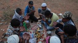 Buruh migran dari Uttar Pradesh berdoa sebelum berbuka puasa selama bulan Ramadan, saat bepergian untuk kembali ke negara asal mereka, selama lockdown untuk mencegah penyebaran Covid-19 di pinggiran Hyderabad, India, Selasa, (12/5/2020). (AP Photo/Mahesh Kumar A)