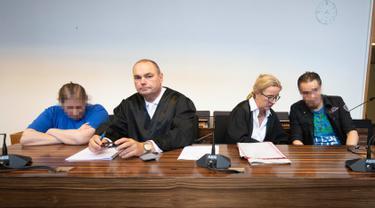 Terdakwa Berrin T (kiri) dan Christian L (kanan) bersama pengacara menunggu sidang putusan di pengadilan distrik di Freiburg, Jerman, Selasa (7/8). Berrin dan Christian diadili karena mencabuli dan menjual putranya ke situs paedofil. (THOMAS KIENZLE/AFP)
