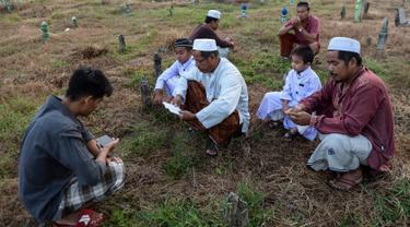 Muslim Thailand berdoa saat menziarahi kuburan kerabat mereka pada perayaan Idul Adha di provinsi Narathiwat, Minggu (11/8/2019). Pada setiap Idul Adha atau menyambut hari besar Islam sebagian warga banyak mendatangi kuburan untuk mendoakan keluarganya. (Madaree TOHLALA/AFP)