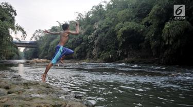 Seorang anak melompat ke Sungai Ciliwung, Depok, Jawa Barat, Kamis (4/7/2019). Menurunnya debit air Sungai Ciliwung akibat musim kemarau dimanfaatkan warga setempat sebagai tempat wisata gratis untuk mengajak anak berenang. (merdeka.com/Iqbal Nugroho)