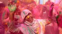 Seorang janda India dengan kerudung bertabur bubuk berwarna-warni saat mengikuti perayaan Holi di kota Vrindavan, India, (9/3). Para janda India dulunya dilarang menghadiri perayaan holi. (AFP Photo / Dominique Faget)