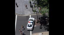 Sebuah mobil polisi menutup jalan di sekitar lokasi penyanderaan di The Lindt Chocolate Cafe, Sydney, Senin (15/12/2014). (Istimewa)
