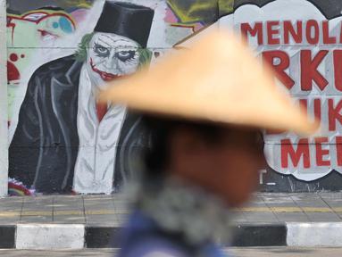 Mural bertulis 'Menolak RKUHP Bukan Menunda' terpampang pada dinding di Jalan Pemuda, Rawamangun, Jakarta, Selasa (1/10/2019). Mural tersebut respons dari seniman Jakarta terhadap RUU KUHP yang dinilai mencederai tatanan demokrasi. (merdeka.com/Iqbal Nugroho)