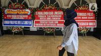 Seorang wanita berjalan dekat karangan bunga di halaman Kantor PT Asuransi Jiwasraya (Persero), Jakarta, Selasa (15/12/2020). Karangan bunga tersebut berisi ucapan dukungan kepada manajemen baru Jiwasraya dalam penyelamatan polis melalui program restrukturisasi. (Liputan6.com/Faizal Fanani)