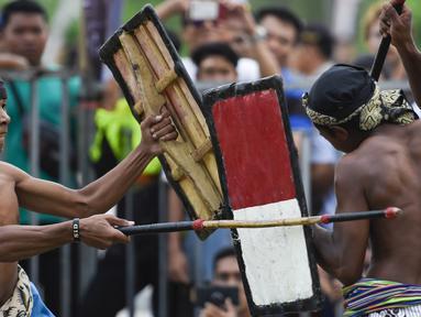 Dua pepadu (petarung) melakukan duel dalam kesenian tradisional peresean di Praya, Lombok Tengah, Selasa (19/2). Peresean merupakan kesenian tradisional suku Sasak yang dulunya diadakan setiap musim kemarau panjang. (MOH EL SASAKY/AFP)