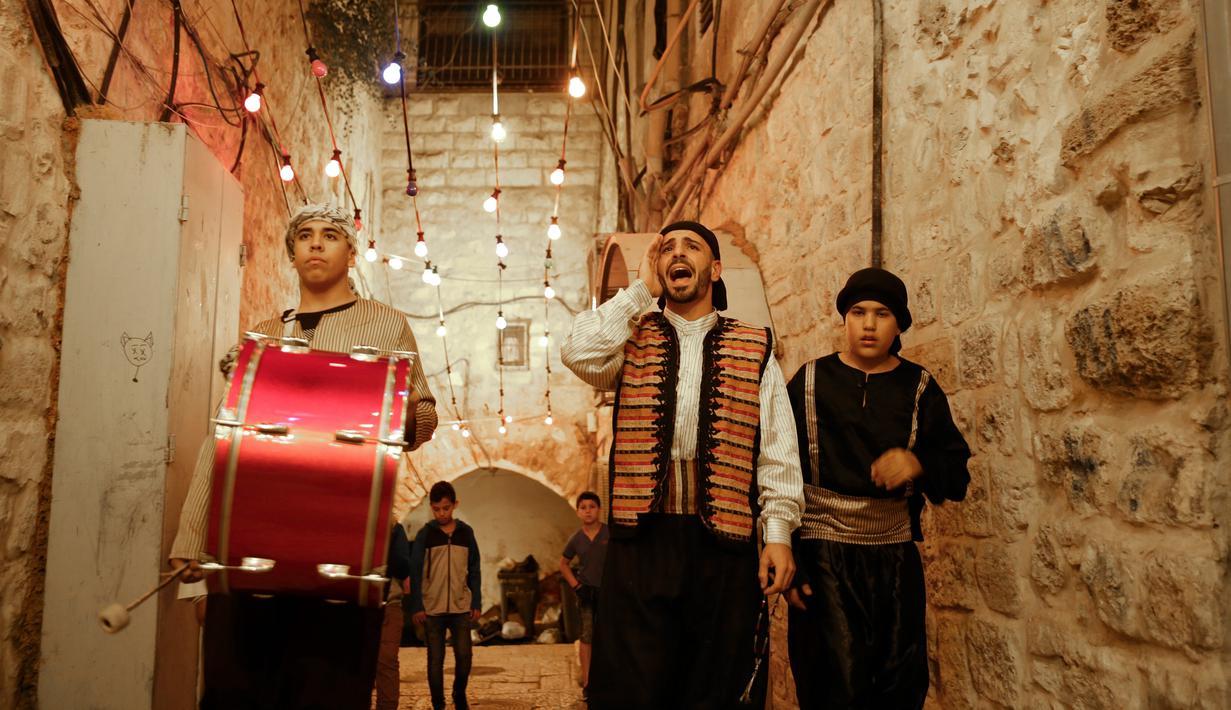 Kelompok pemuda Palestina mengenakan pakaian tradisional berteriak membangunkan kaum muslim untuk sahur di Kota Tua Yerusalem, Selasa (5/6). Membangunkan sahur atau Musaharati sudah menjadi tradisi yang dilakukan secara turun-temurun. (AP/Mahmoud Illean)