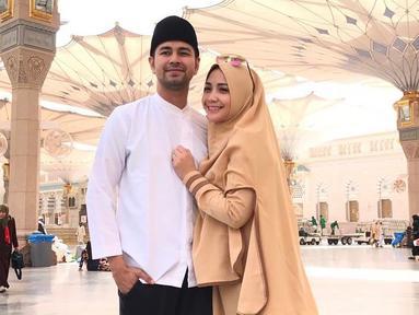 Nagita Slavina tetap terlihat stylish dan fashionable dengan memakai hijab syari di tanah suci saat umrah bersama sang suami. Keduanya pun tampak mesra dan lengket bak pasangan muda-mudi. Hijab berwarna oranye tersebut nampak sangat cocok ia kenakan. (Liputan6.com/IG/@raffinagita1717)