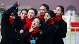 Sejumlah wanita berswafoto saat pembukaan Kongres Rakyat Nasional di Beijing, China, Minggu (3/3). Kongres ini digelar setiap tahun. (AP Photo/Andy Wong)