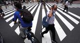 Orang-orang yang memakai masker untuk mencegah penyebaran COVID-19 meyeberang jalan di Shibuya, Tokyo, Jepang, Jumat (3/7/2020). Jepang mengangkat darurat pandemi selama tujuh minggu pada akhir Mei, sebagian besar kegiatan sosial dan bisnis sejak itu telah kembali dimulai. (AP Photo/Eugene Hoshiko)