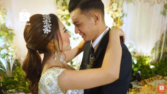 Senyum bahagia Nella dan Dory setelah resmi menjadi suami istri. Sebelumnya, pasangan ini membuat penasaran para penggemarnya lantaran kedekatannya. (Youtube/SHOPEE Indonesia)