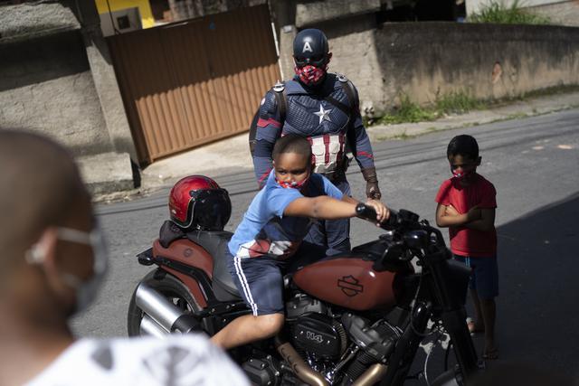 Seorang anak duduk di atas sepeda motor Everaldo Pinto, petugas polisi militer yang berkostum superhero Captain America di Petropolis, Rio de Janeiro, Brasil, Kamis (15/4/2021). Pinto memberitahu anak-anak tentang perlunya melindungi diri dari virus corona. (AP Photo/Silvia Izquierdo)