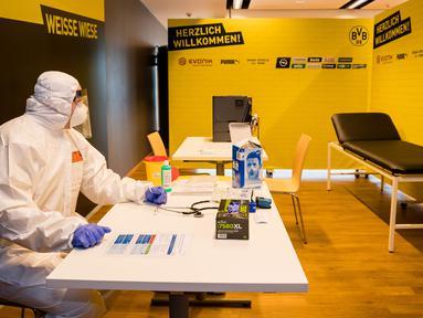 Seorang staf medis mengenakan pakaian APD duduk di dalam pusat pengujian COVID-19 di stadion milik Borussia Dortmund di Dortmund, Jerman (3/4/2020). Stadion milik Borussia Dortmund dialihfungsikan menjadi tempat pusat pengujian COVID-19 mulai Sabtu (4/4). (Xinhua/Borussia Dortmund/Alexandre Simoes)