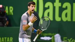 Petenis Serbia, Novak Djokovic bereaksi saat melawan petenis Skotlandia, Andy Murray dalam final turnamen Qatar Terbuka di Doha, Sabtu (7/1). Novak Djokovic sukses menang dalam pertarungan melelahkan selama 3 jam. (AP Photo/Alexandra Panagiotidou)