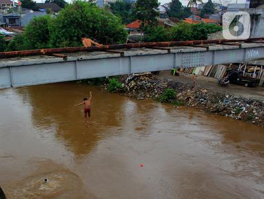 Seorang anak nekat melompat dari jembatan ke Kali Ciliwung Kalibata, Jakarta, Selasa (25/2/2020). Kali Ciliwung meluap usai hujan deras mengguyur Jakarta dan sekitarnya pada kemarin malam. (merdeka.com/magang/Muhammad Fayyadh)