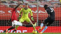 Striker Aston Villa, Keinan Davis (kanan) melepaskan tendangan yang berhasil diblok bek Manchester United, Eric Bailly dalam laga lanjutan Liga Inggris 2020/21 pekan ke-17 di Old Trafford, Jumat (1/1/2021). Aston Villa kalah 1-2 dari Manchester United. (AFP/Carl Recine/Pool)