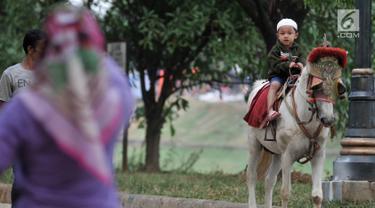 Seorang anak menunggangi kuda di kawasan Kanal Banjir Timur, Jakarta, Selasa (5/6). Berkuda mengelilingi kawasan Kanal Banjir Timur menjadi salah satu pilihan warga untuk ngabuburit sembari mengajak anak-anak bermain. (Merdeka.com/Iqbal S. Nugroho)