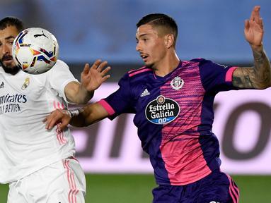 Bek Valladolid, Javi Sanchez (kanan) berebut bola dengan pemain depan Real Madrid, Karim Benzema pada lanjutan La Liga Spanyol di stadion Alfredo, Rau (30/9/2020). Real Madrid menekuk Real Valladolid denga skor 1-0. (PIERRE-PHILIPPE MARCOU / AFP)