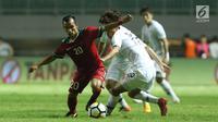 Pemain sayap Timnas Indonesia U-23. Riko Simanjuntak (kiri) berebut bola dengan pemain Korea Selatan U-23 pada laga persahabatan di Stadion Pakansari, Kab Bogor, Sabtu (23/6). Babak pertama Indonesia U-23 tertinggal 0-1. (Liputan6.com/Helmi Fithriansyah)