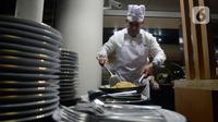 Ketua KPK, Firli Bahuri menunjukkan keahliannya memasak nasi goreng untuk dibagikan kepada para pimpinan KPK dan Dewan Pengawas saat acara silaturahmi di Jakarta, Senin (20/1/2020). Firli yang biasanya mengenakan jas dan kemeja, kini mengenakan celemek dan topi koki. (merdeka.com/Dwi Narwoko)