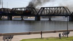 Kereta barang tergelincir dan terbakar di jembatan Danau Kota Tempe, Arizona, Amerika Serikat, Rabu (29/7/2020). Kecelakaan memicu kebakaran hebat dan terlihat beberapa kilometer. (AP Photo/Ross D. Franklin)