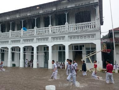 Siswa SMK 1 Budi Utomo beraktivitas di tengah genangan hujan yang merendam sekolah mereka, Jakarta, Senin (9/2/2015). (Antara Foto/Fanny Octavianus)